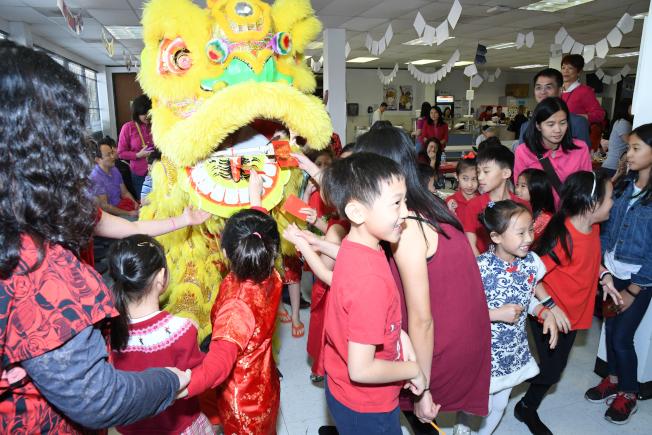 中華文化中心春節聯歡祥獅忽然出現,小學生們驚喜萬分,紛紛餵送紅包,祈求吉利。