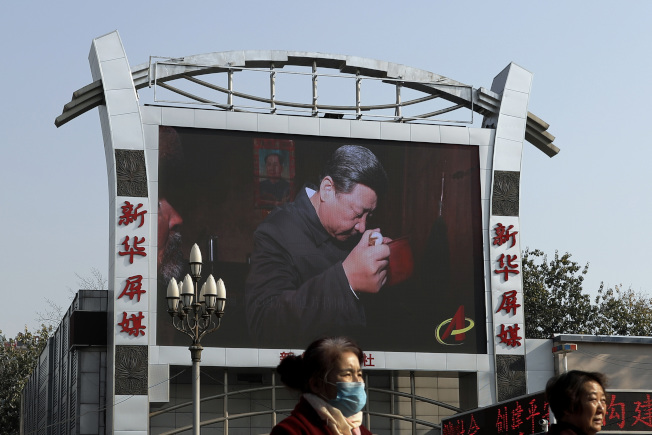 北京火車站旁的大屏幕播放習近平訪問農村的紀錄片。(美聯社)
