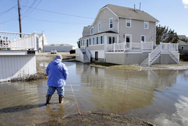 在第三場暴風雪接踵而來之際,麻州杜斯柏瑞鎮有些地區的淹水仍未消退。(美聯社)