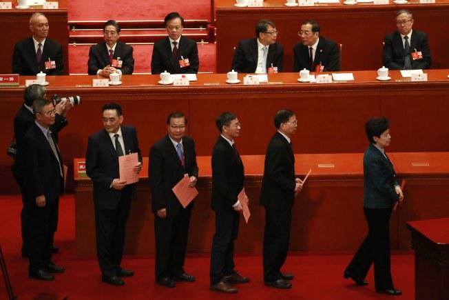 中國全國人大11日就修憲草案進行表決,代表排隊依序準備投票。(歐新社)