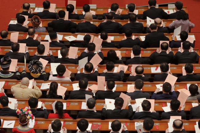 中國全國人大11日就憲法修正案進行表決前,與會代表查看手中的選票。(路透)