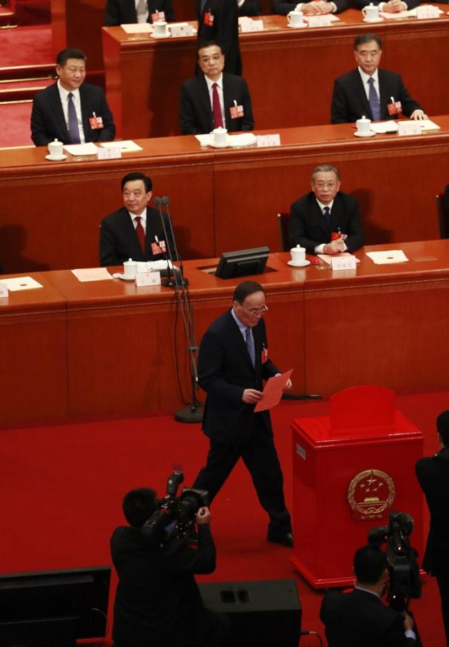 中國全國人民代表大會11日就憲法修正案進行表決,國家主席習近平(最後排左)、總理李克強(最後排中),看著中國共產黨中央紀律檢查委員會書記王岐山投票。(歐新社)