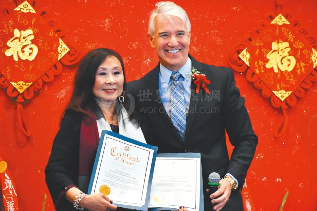 地方檢察長賈斯康(圖右)向舊金山上海協會會長李美玲頒贈賀狀,嘉許她致力推動改善肖化區治安。(記者李秀蘭/攝影)
