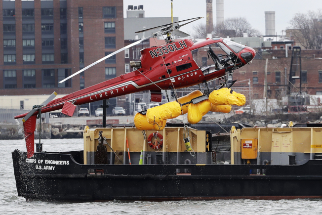 紐約市11日發生的觀光直升機墜河事件,墜機原因疑為一名乘客的背袋誤觸燃油緊急切斷開關。圖為起重機把失事直升機吊上駁船。(美聯社)