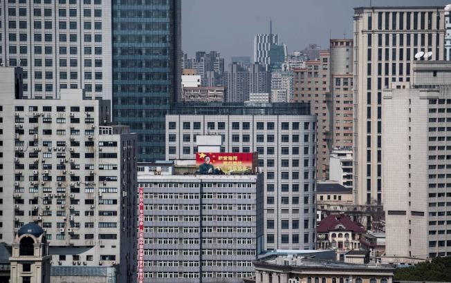 中共人大剛通過修憲案。上海市區裡一棟高聳大樓張貼的宣傳畫布上,印著國家主席習近平的畫像,一旁是長條紅帶標語。(Getty Images)