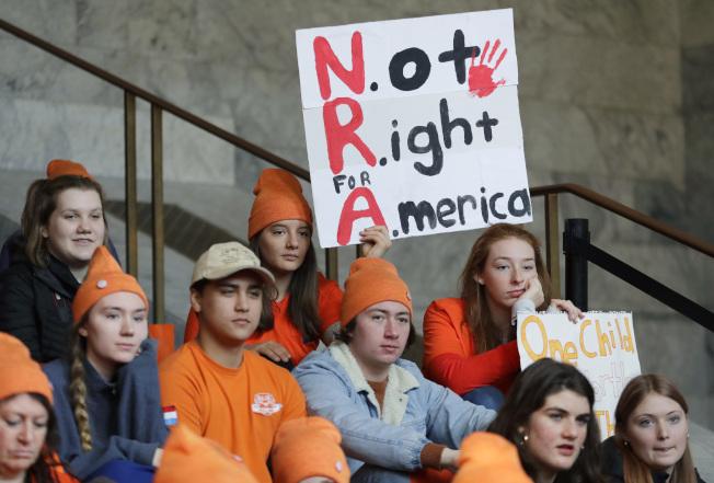 要求管制槍枝的學生日前在華盛頓州首府奧林匹亞一場集會上,舉著「全國步槍協會─不適合美國」的標語,要求州長簽署管制槍枝法案。(美聯社)