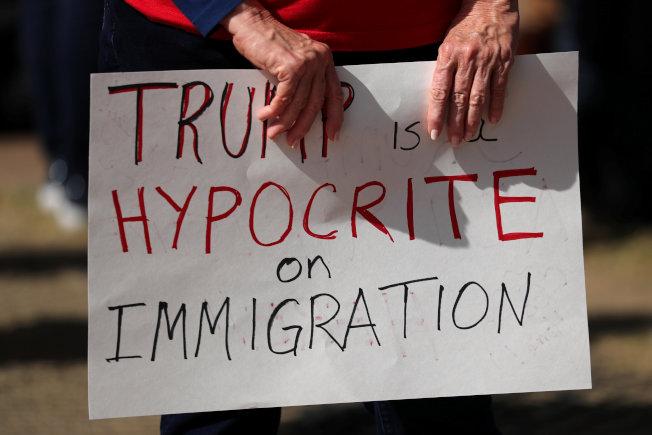 一位民眾拿著「川普是移民政策的偽君子」標語,抗議即將到加州訪問,並視察阻擋移民的邊牆工程進度。(路透)