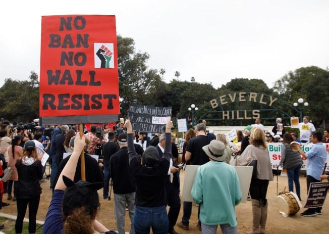 總統川普13日訪問加州視察邊牆模型,移民維權團體12日在洛磯比佛利山莊前抗議。(歐新社)
