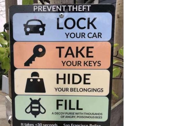 舊金山一塊告示牌建議車主在車內放一個「裝滿毒蜂」的錢包防爆竊。(電視新聞截圖)