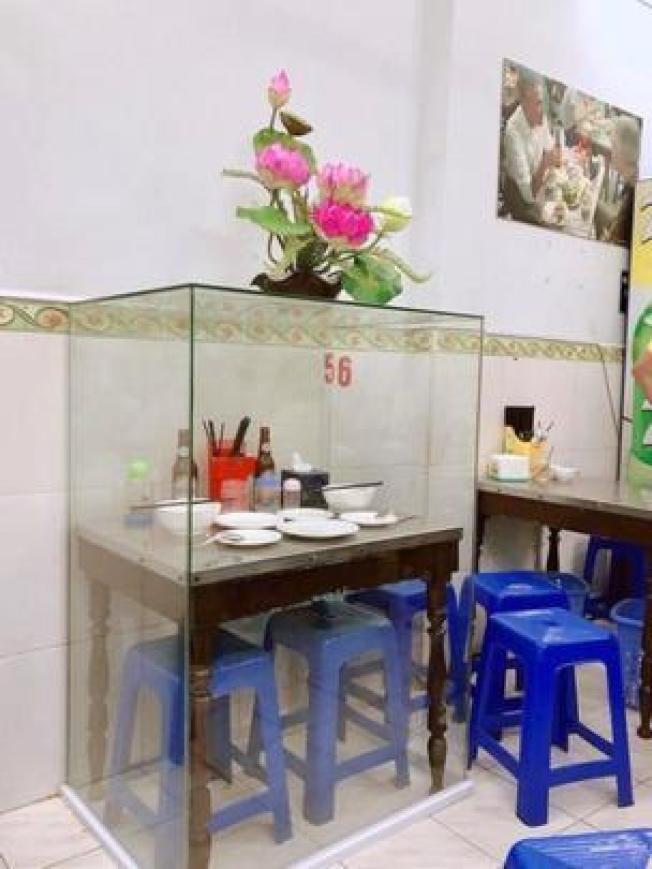 店家把歐巴馬和波登用餐過的桌椅和餐具用透明櫃「封存」。(取自臉書)