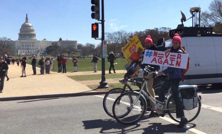 全國反槍枝暴力集會「為活命而走」(March for Our Lives),主場華府今天中午在賓州大道展開。圖為維州夏洛茲維爾一對年輕夫婦騎單車反槍示威。(特派員許惠敏/攝影)