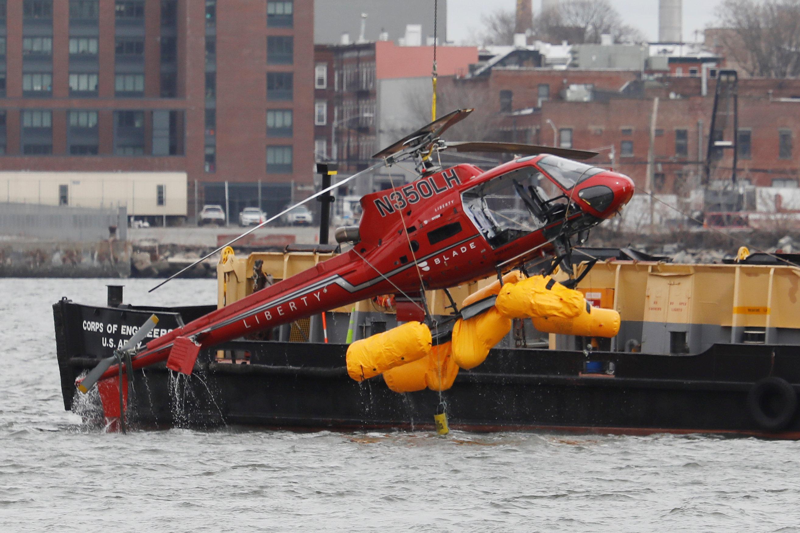 圖為直升機殘骸被吊起。路透