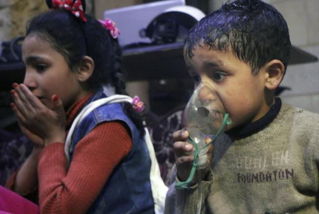 敘利亞反抗軍占領的東古塔地區最大城鎮度瑪鎮遭毒氣攻擊,許多幼童喪命。圖為受襲擊的幼童在救護中心治療時使用呼吸器。(Getty Images)