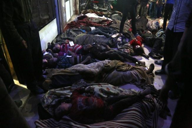 遭到毒氣殺害的敘利亞度瑪鎮居民的屍體排列一起。(歐新社)