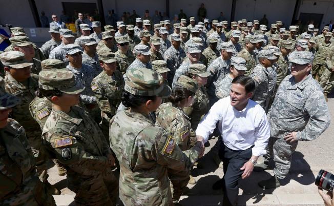 亞利桑那州共和黨州長杜西9日宣布,亞州首批225名國民兵向邊界地區開拔,以執行川普總統部署邊界的命令。圖為杜西(穿白上衣者)向即將出發的國民兵握手致意。(美聯社)