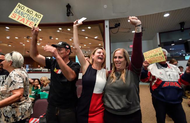 加州橙縣在投票加入司法部的訴訟,以對抗州府的庇護法律後,縣議會官員一同慶祝。(美聯社)