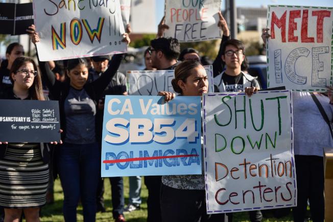 支持庇護州政策的民眾在加州聖塔安那縣議會門外舉牌抗議。(美聯社)