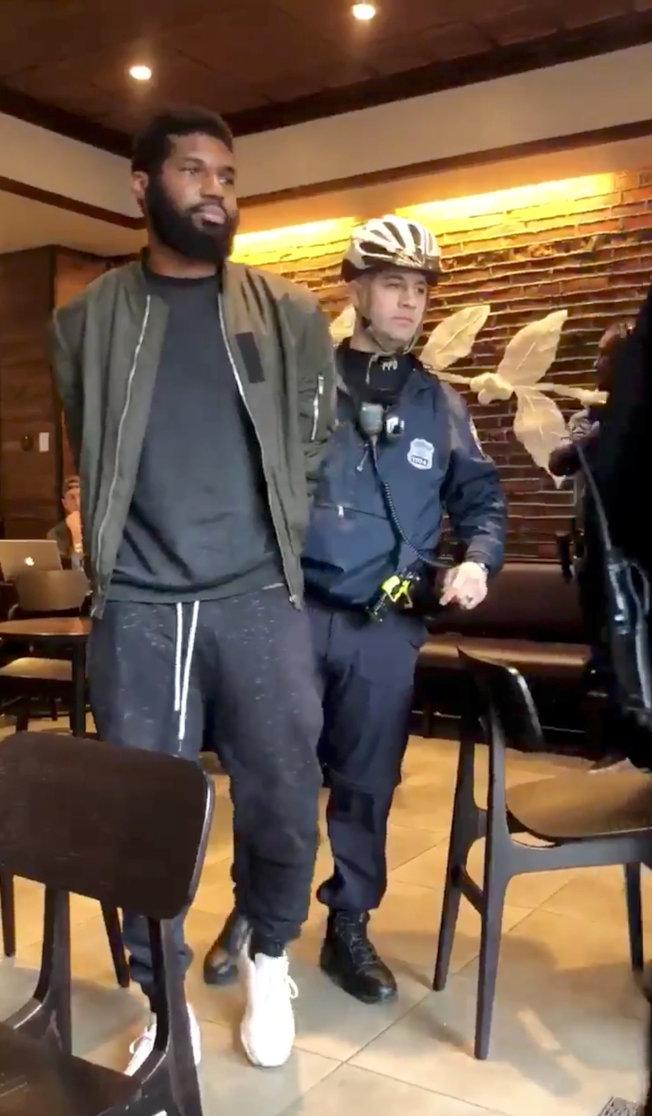 社群網路所傳的照片顯示費城警員12日逮捕一名在費城星巴克咖啡店的非洲裔男子。(路透)