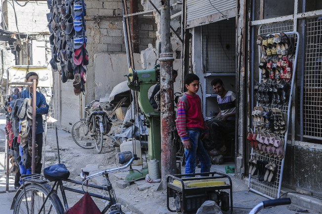 被敘利亞政府軍攻陷的古塔市癖瑪鎮,居民打開店門,要過日子。(歐新社)