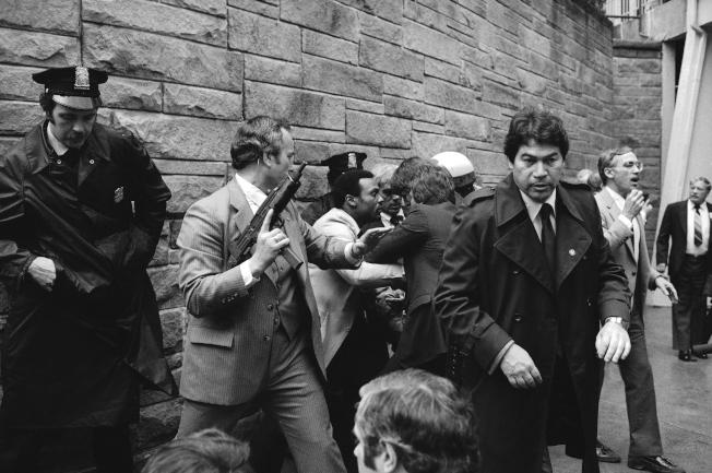 雷根於1981年3月在華府遇刺,在場執法人員撲倒槍手,一名特勤局探員舉起自動武器戒備。(美聯社)