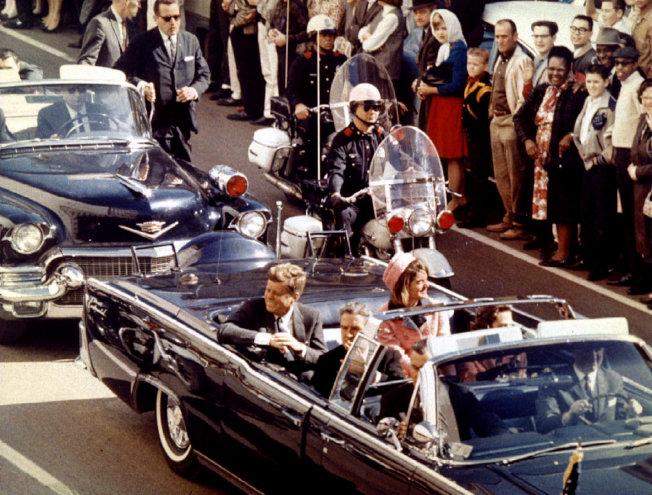 甘迺迪遇刺前,與夫人賈桂琳一起坐在車內,接受達拉斯居民夾道歡迎。(路透)