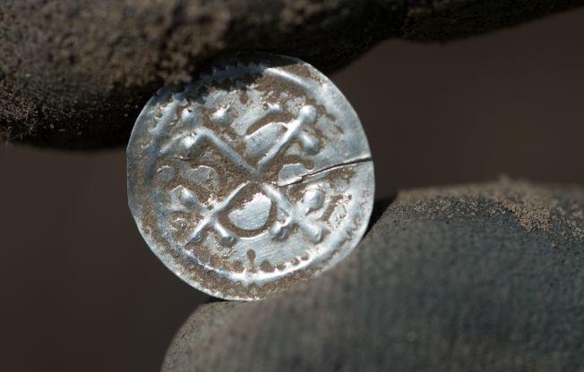 圖為13歲男孩和業餘考古學家在德國挖到一枚閃閃發光的銀幣。Getty Images