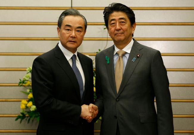 日本首相安倍晉三(右)16日在官邸與大陸國務委員兼外交部長王毅(左)會面。(Getty Images)