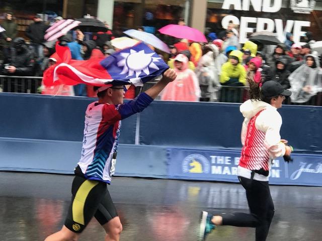 第122屆波士頓馬拉松比賽16日在強風大、攝氏三度低溫下進行,嚴厲考驗來自台灣的選手。麻州波克萊臺灣商會、駐波士頓台北經濟文化辦事處官員及選手家屬在馬拉松賽終點線前設置的加油站,將中華民國國旗遞給衝線的台灣選手。經文處長徐佑典也在風雨中替參賽的臺灣選手加油打氣,並為他們的表現感到驕傲。徐佑典說,臺灣代表團來波士頓參加馬拉松大賽,也身負著國民外交任務。親睹許多選手在終點披著中華民國國旗衝線,心情非常興奮與感動,選手的表現大幅增加臺灣在國際上的能見度。在賽前,徐佑典也參加與波克萊臺灣商會共同舉辦的晚宴,歡迎參加本屆波馬的台灣選手暨親友。今年臺灣選手中有兩位視障選手、10位女性選手,更有七名跑者可望在波馬完賽後,獲得全球六大馬(波士頓、倫敦、柏林、芝加哥、紐約、東京)的「六星跑者」。圖為台灣選手披國旗跑向終點。(圖由經文處提供)