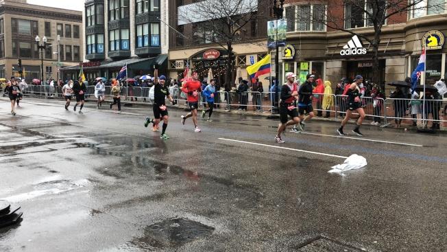 2018波士頓馬拉松在風雨中開跑,跑者與到場觀眾熱情互動。(記者劉晨懿之/攝影)