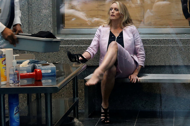 成人片豔星雨丹尼爾斯16日到紐約聯邦法庭旁聽,經過安檢後穿上鞋子。(路透)