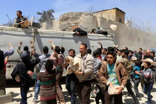 敘利亞政府軍已攻占東古塔鎮,趕走反抗軍。圖為政府工作人員16日在當地發送麵包。(Getty Images)