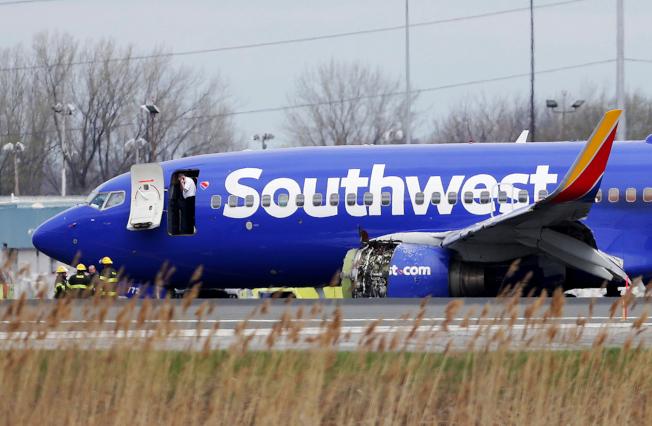西南航空公司班機迫降後,一名機師在機門口打電話。(美聯社)