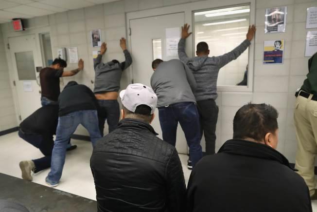 被捕的無證移民接受ICE探員搜身。(Getty Images)
