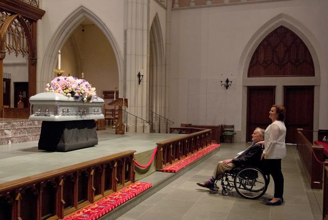 休士頓聖馬丁主教教堂20日開放民眾悼念前第一夫人芭芭拉‧布希。圖為前總統老布希在民眾入場前,在女兒桃樂絲‧布希‧柯奇陪伴下,坐著輪椅,默默望著芭芭拉的靈柩。(美聯社)