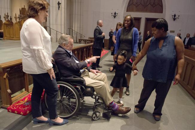休士頓聖馬丁主教教堂20日開放民眾悼念前第一夫人芭芭拉‧布希。圖為前總統老布希坐在靈柩旁的輪椅上,向民眾答禮。(美聯社)
