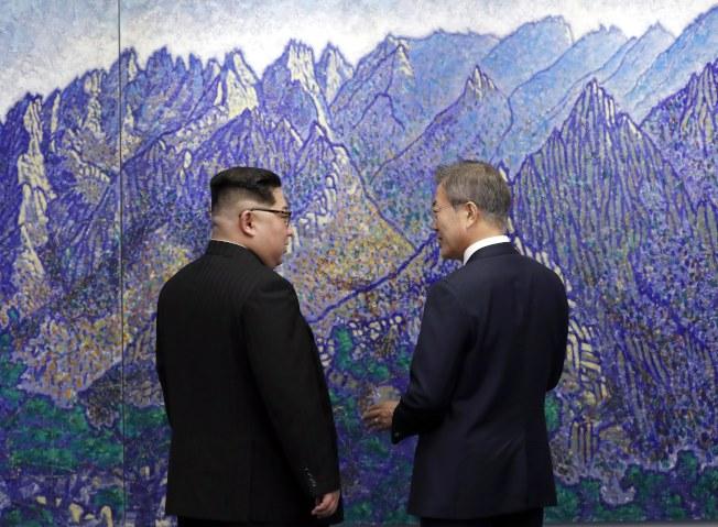 金正恩(左)與文在寅(右)27日上午在板門店和平之家,在峰會開始前對著壁畫閒談。歐新社
