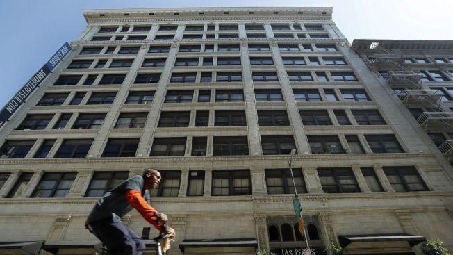 一民眾騎單車經過洛杉磯市中心第六街上Santa Fe Lofts大樓,該物業剛以近7000萬元價格出售,這是近年來隨著租金上漲,出現的市中心轉型一部分。(洛杉磯時報)