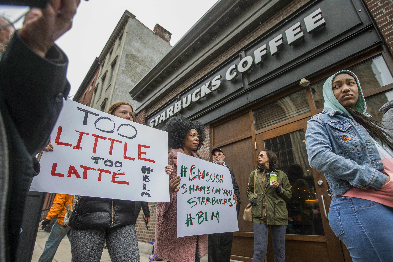 兩名非裔日前在費城星巴克分店未消費卻要求如廁被拒,該店隨後召來警察,警察將兩人扣上手銬逮捕。圖為15日費城星巴克市中心分店外示威者舉牌抗議。美聯社