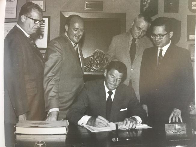當時還是州長的雷根(Ronald Reagan)簽署譚卓儀(右一)的「教育補償計畫」提案。(譚卓儀提供)
