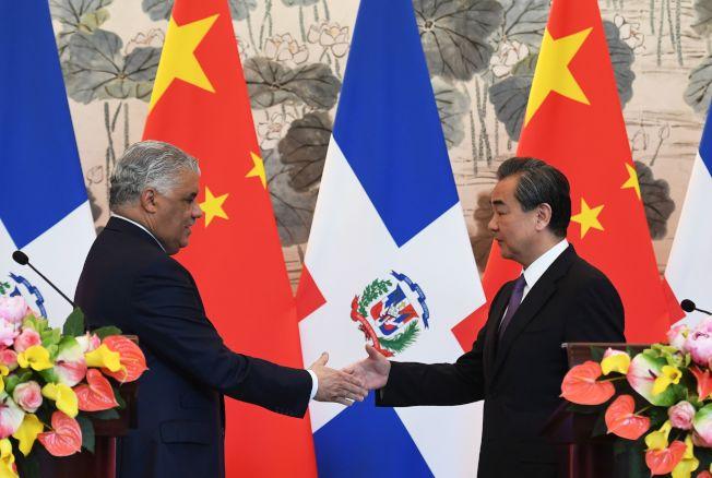 中國外交部長王毅(右)與多明尼加外長瓦嘉斯1日在北京握手。(Getty Images)