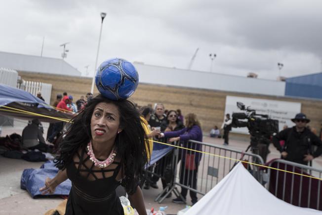 司法部長塞辛斯2日增派檢察官、名法官鎮守美墨邊境海關,阻擋來自中美洲的「大篷車」移民大軍入境。圖為一名等待來美的女子趁閒玩足球。(美聯社)