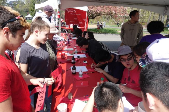 中國學生為遊客寫中文名。(記者謝哲澍/攝影)