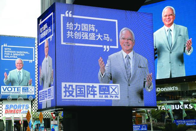 馬來西亞首都吉隆坡鬧區隨處可見總理納吉的宣傳看板,還有中文訴求華裔選民。(美聯社)