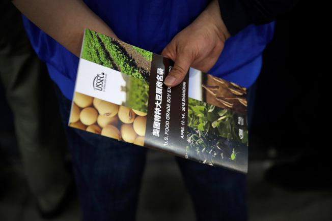 媒體報導,川普總統在中興通訊案上讓步,換取中國取消對美國大豆課高額進口關稅。圖為美國大豆協會月前在上海的國際展銷會上推出中文說明。(美聯社)