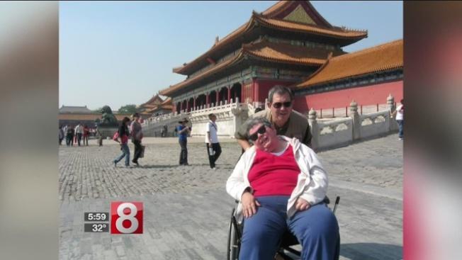 費利特在近30年內,帶著半癱妻子唐娜環遊世界,造訪20多個國家。圖為他們在北京故宮合影。(電視截圖)