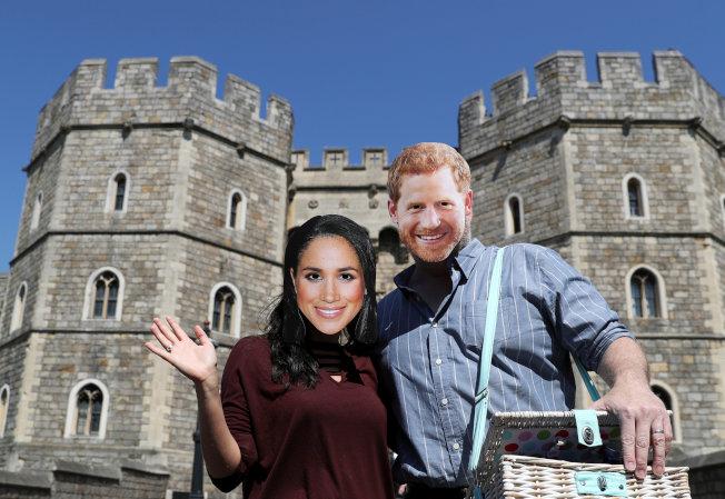 一對遊客戴上哈利王子與梅根的面具,在溫莎堡前玩自拍。(路透)