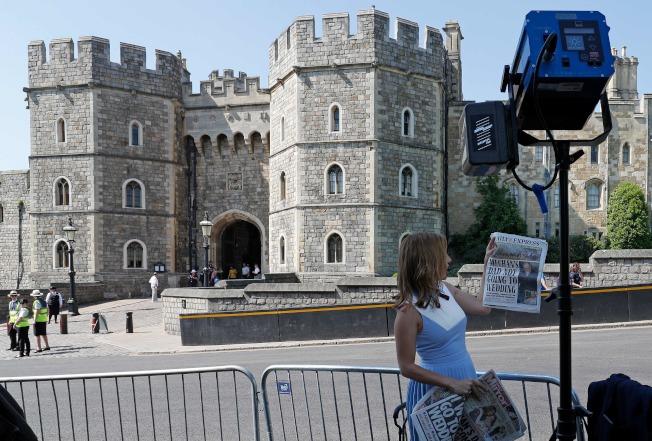 美國CNN記者在溫莎堡前面舉著英國報紙說,梅根的父親是否出席女兒婚禮,已造成皇室困擾。(Getty Images)