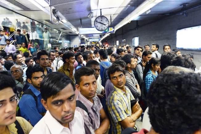 根據聯合國的預估,印度德里將在2028年取代日本東京,成為全球人口數最多的大都市,圖為在新德里火車站等車民眾。(法新社)