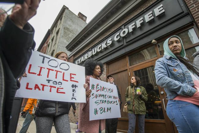 費城星巴克咖啡店召警逮捕兩名非裔事件傳出後,引發居民不滿,在店外擔牌抗議。(美聯社)