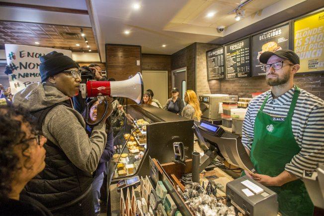 抗議民眾帶著擴音器到這間召警逮人的星巴克咖啡店嗆聲。(美聯社)